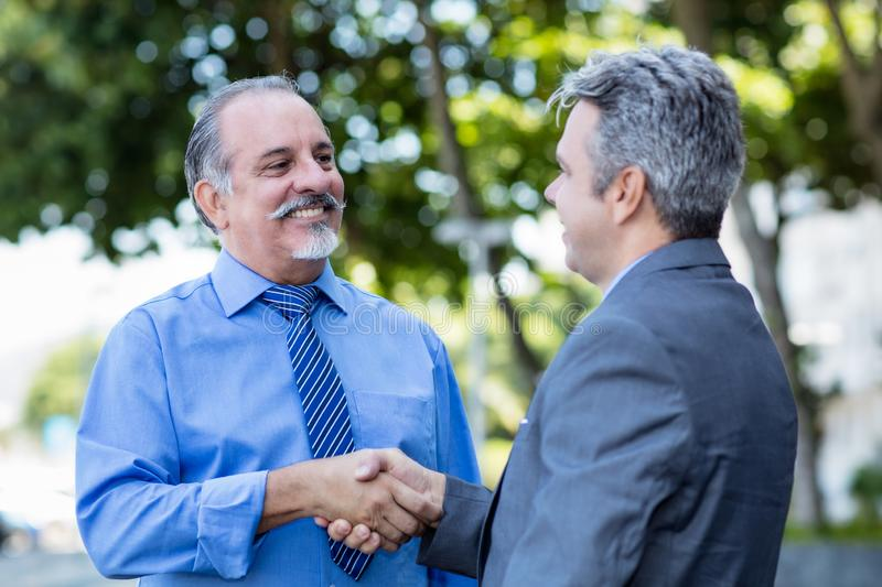 Handshake of senior businessman and mature man in suit stock photo