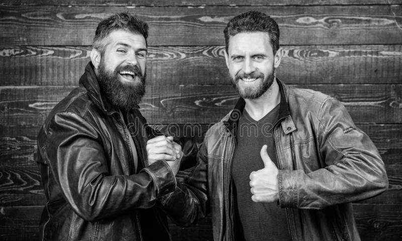 Handshake symbol of successful deal. Have agreed. Brutal bearded men wear leather jackets shaking hands. Strong stock image