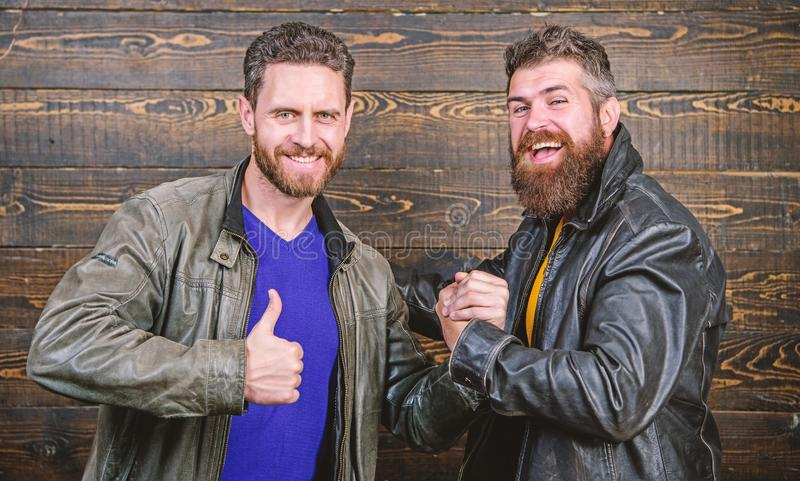 Handshake symbol of successful deal. Have agreed. Brutal bearded men wear leather jackets shaking hands. Strong royalty free stock photos