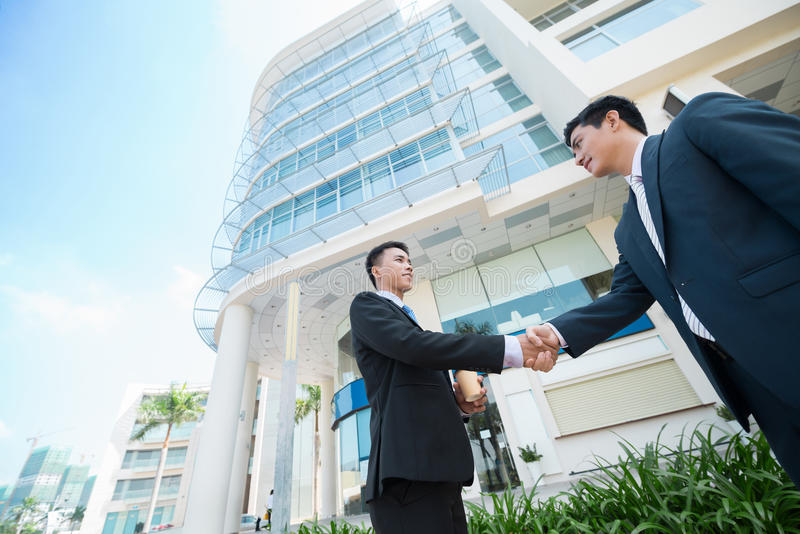 Handshake. Two Asian businessmen shaking their hands, view from below stock image