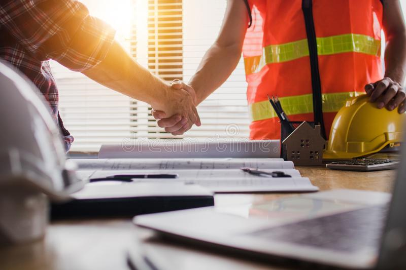 Handshake of two business man, after  architect working and planning blueprint, Engineering objects on workplace stock images