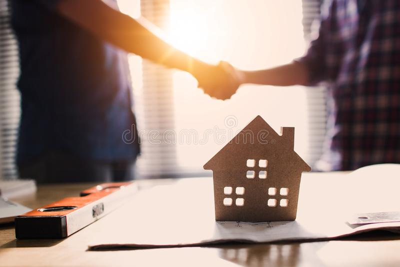 Handshake of two business man, after  architect working and planning blueprint, Engineering objects on workplace stock photography