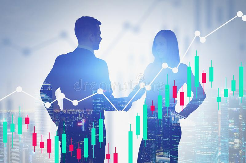 Handshake of two business partners in city, charts. Silhouettes of smiling young businesswoman and her bearded partner shaking hands in night city with double stock images