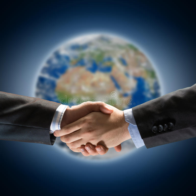 Handshake of two businessmen. On the background of the planet earth. Elements of this image are furnished by NASA stock photos