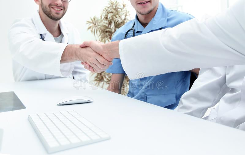 Handshake between the two doctors during the working meeting royalty free stock photography