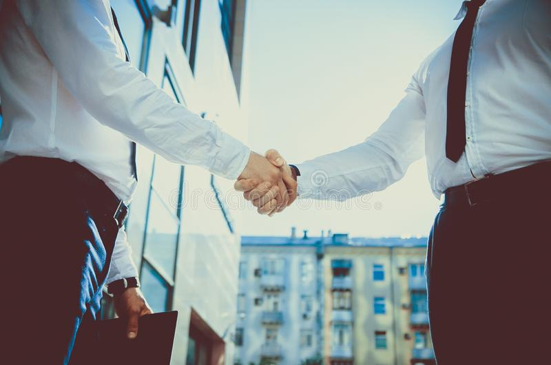 Handshake of two young men against a multi-storey office building. Make a deal. Friendly relations. Office staff. Signing royalty free stock image