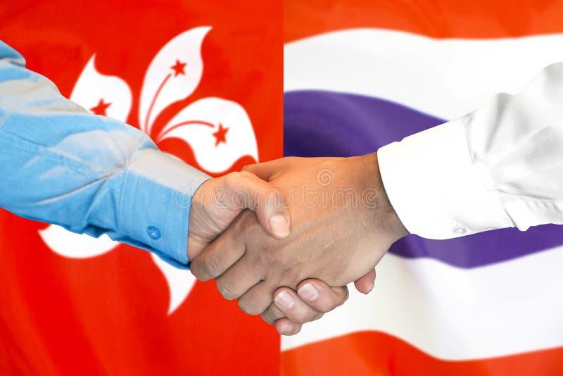 Handshake unter der Flagge Hongkongs und Thailands stockfotos