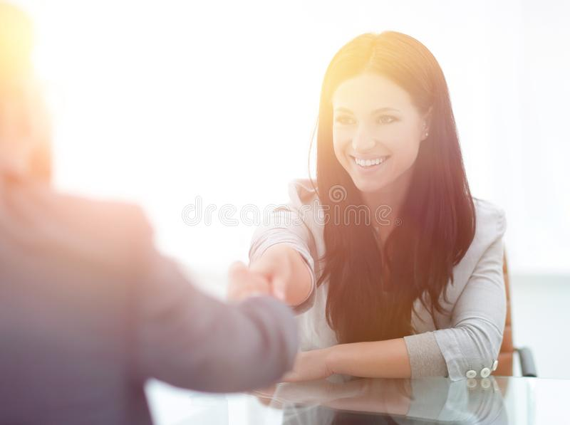 Handshake young business woman with a partner in the office royalty free stock image