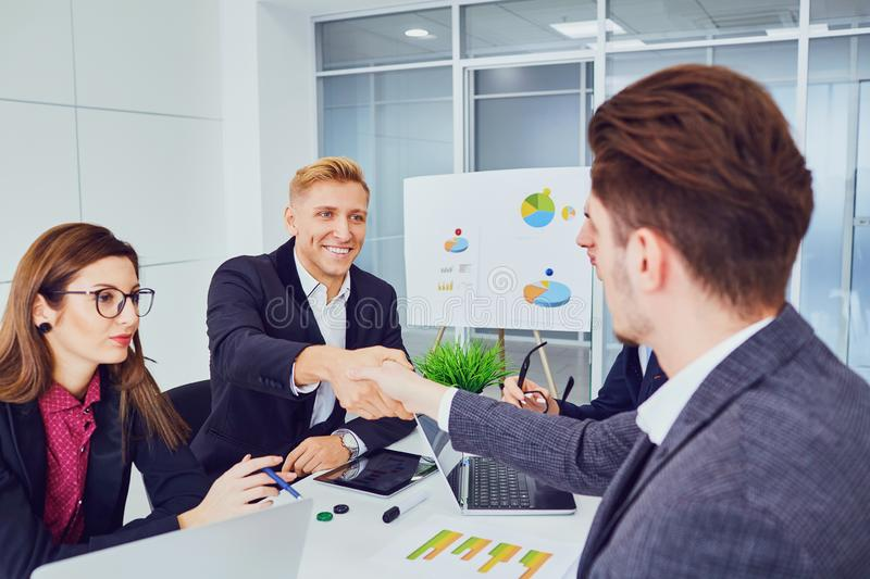 Handshake of young businessmen at a meeting of partners in an office. royalty free stock photos