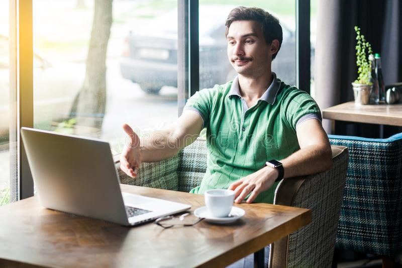 Handshake. Young satisfied businessman in green t-shirt sitting, looking at laptop screen, giving hand to greeting on interview. Video call meeting. business stock images