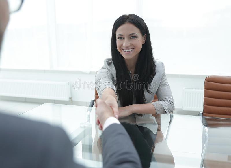 Handshake of a young woman with a business partner royalty free stock photo