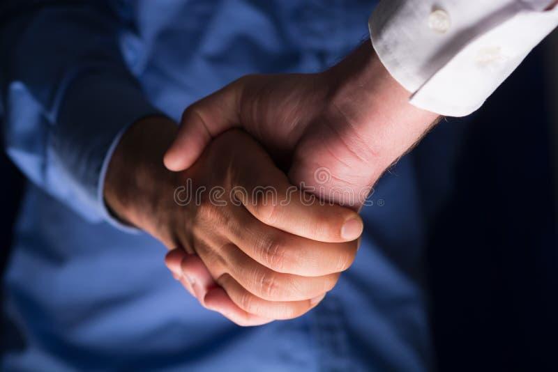 Handshaking рукопожатия в темноте с нижним светом стоковое изображение