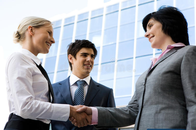Handshaking. Photo of successful businesswomen handshaking after striking deal while happy man looking at them royalty free stock photo