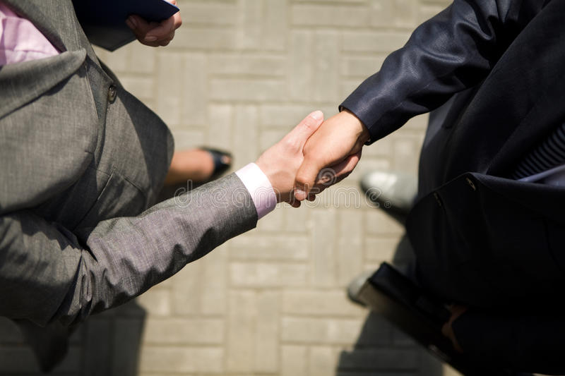 Handshaking. Above view of successful business partners handshaking after striking deal royalty free stock photography