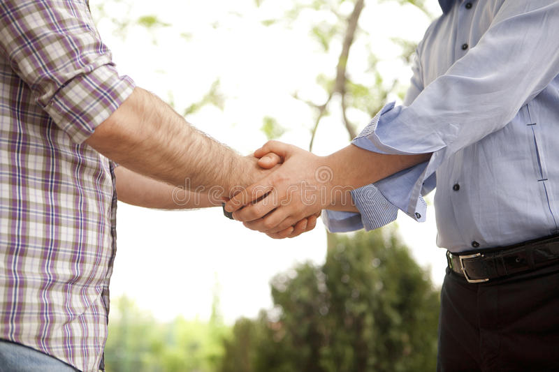 Handshaking. Natural outside and sincere handshaking stock photos