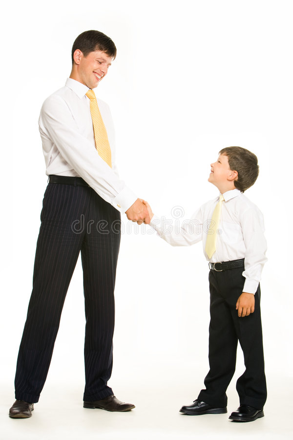 Handshaking. Portrait of father and son standing and handshaking while looking at each other on white background royalty free stock photography