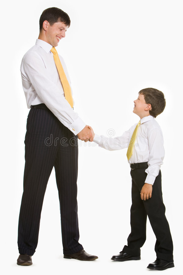 Handshaking. Portrait of father and son standing and handshaking while looking at each other on white background royalty free stock image