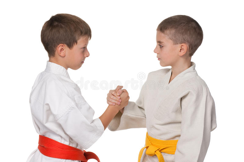 Handshaking boys in kimono. A portrait of handshaking boys in kimono; isolated on the white background stock images