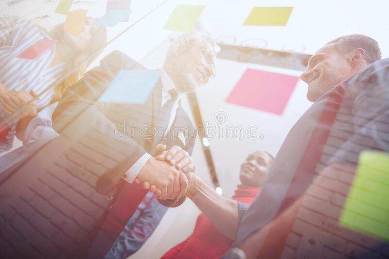 Handshaking business person in office. concept of teamwork and partnership. stock image
