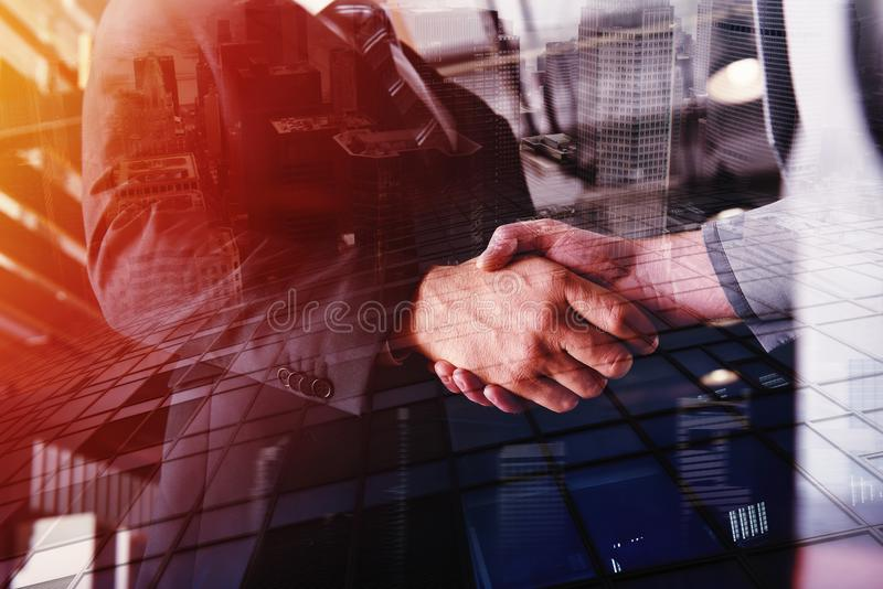 Handshaking business person in office. concept of teamwork and partnership. double exposure stock photos