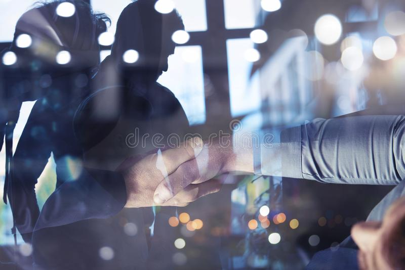 Handshaking business person in office. concept of teamwork and partnership. double exposure. Handshaking business person in the office. concept of teamwork and royalty free stock photo