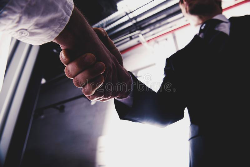 Handshaking business person in office. concept of teamwork and partnership. Handshaking business person in the office. concept of teamwork and business royalty free stock photo