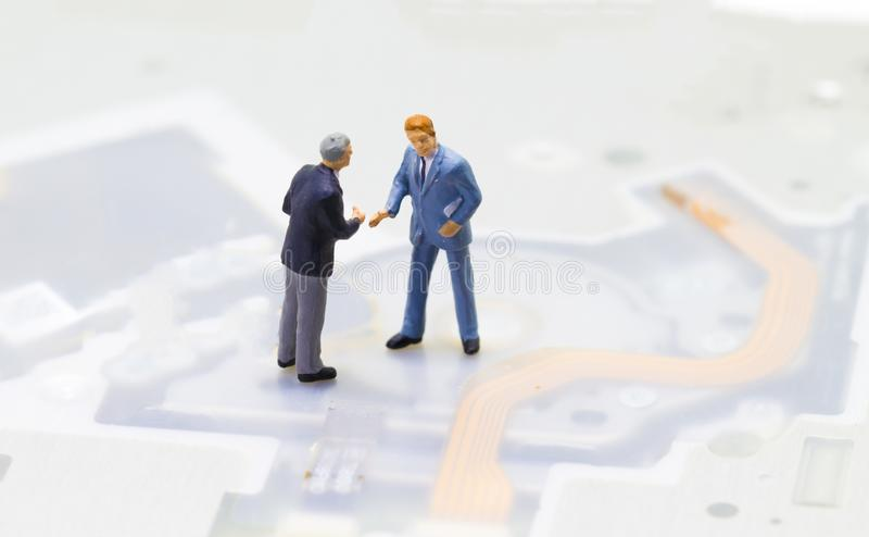 Handshaking businessmen and technology background. Computing or internet industry. royalty free stock photography