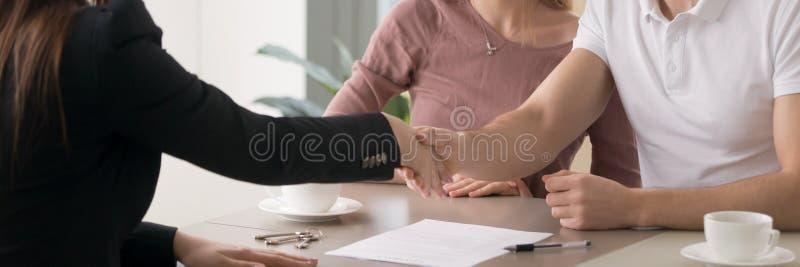 Handshaking för avtal för fastighet för horisontalfotopar undertecknande med fastighetsmäklare arkivfoto