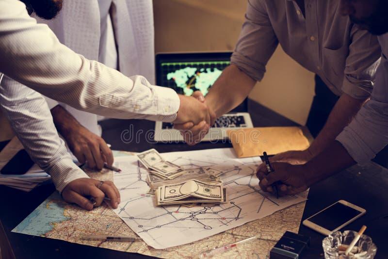 Handshaking för grupp människordanandeöverenskommelse över översikt och pengar royaltyfria foton