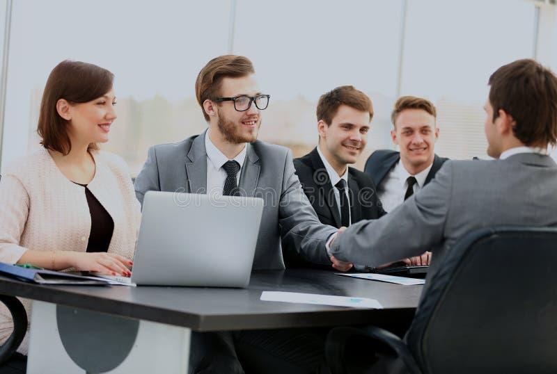 Handshaking för två säker affärsmän och le, medan sitta på tabellen samman med deras kollegor royaltyfri bild
