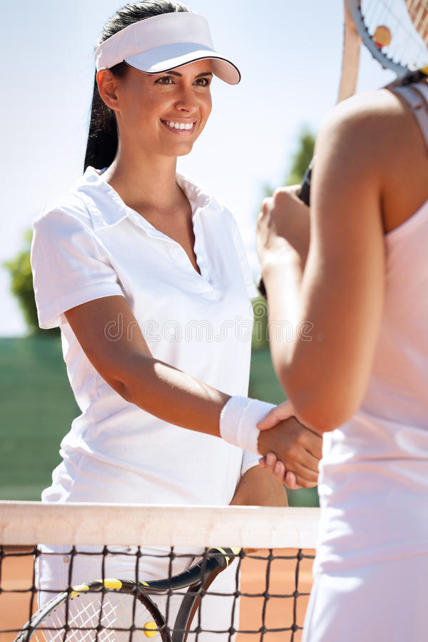 Handshaking after fair match. Women handshaking after playing a tennis match royalty free stock image