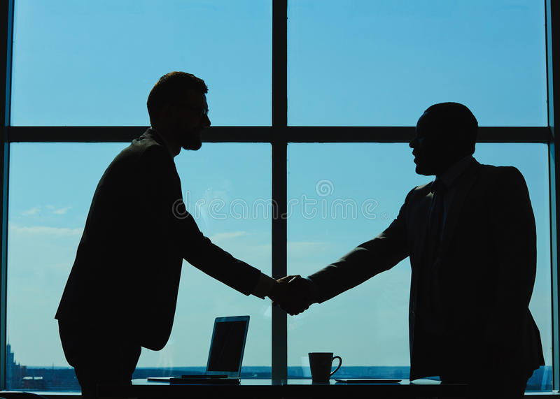 Handshaking. Outlines of two businessmen handshaking against window royalty free stock images