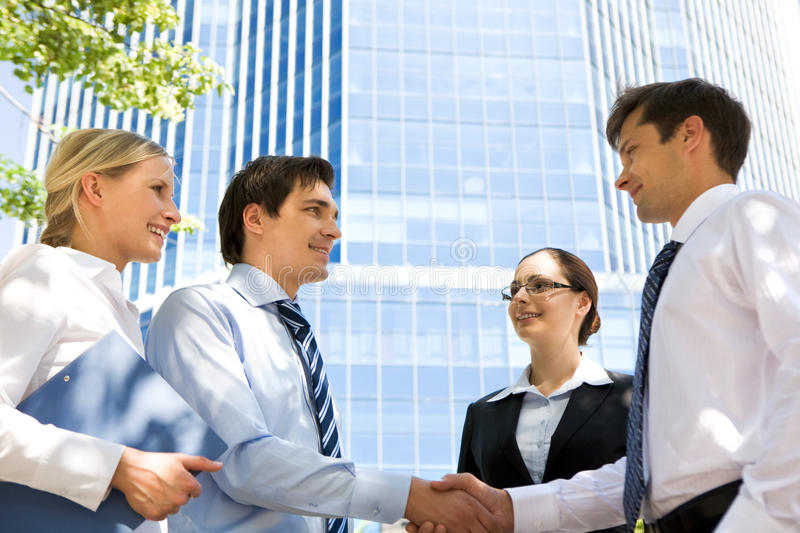 Handshaking partners. Photo of successful associates handshaking after striking deal outdoors at meeting royalty free stock photos