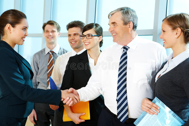 Handshaking partners. Photo of successful associates handshaking after striking deal with partners near by royalty free stock photography