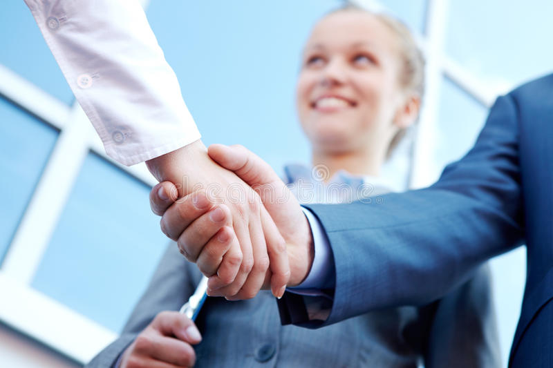 Handshaking partners. Photo of successful associates handshaking after striking deal outdoors at meeting stock photography