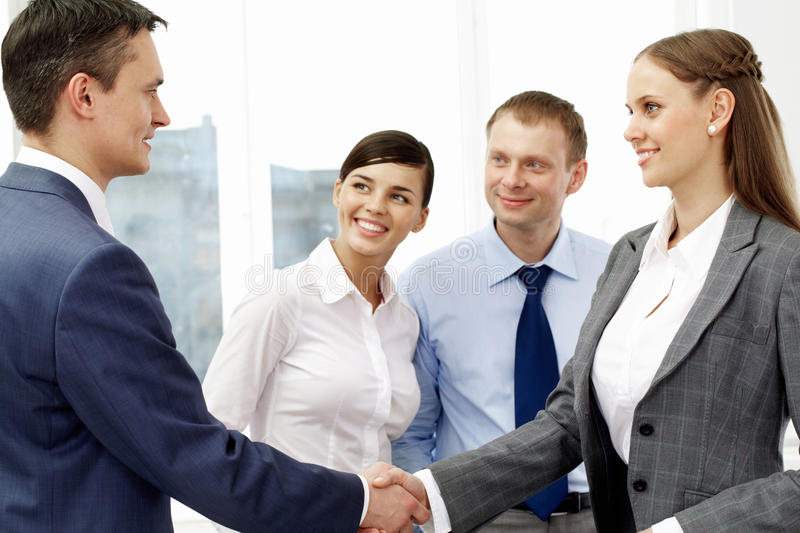 Handshaking partners. Photo of successful associates handshaking after striking deal with partners near by royalty free stock image