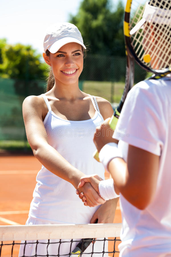 Handshaking at the tennis court after a match. Two women handshaking at the tennis court after a match royalty free stock photography