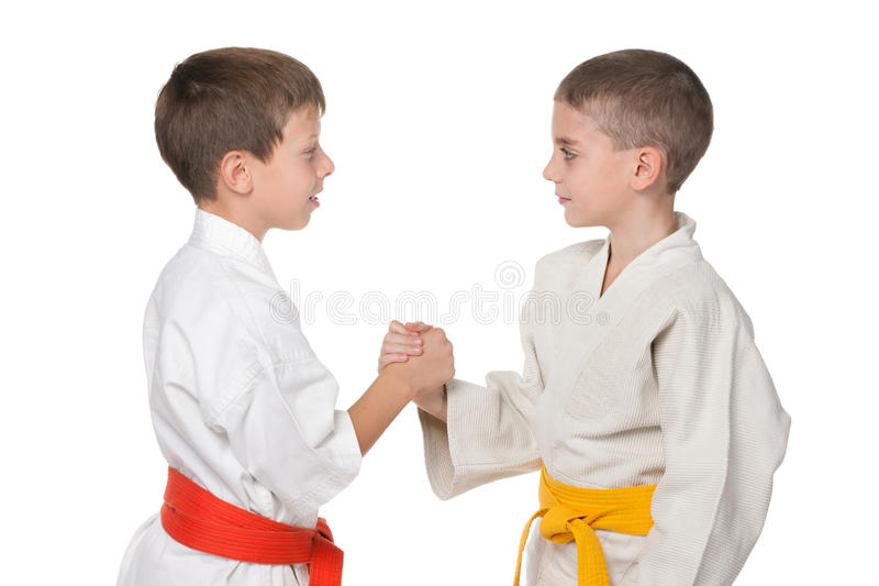 Handshaking of two boys in kimono. A portrait of handshaking boys in kimono against the white background royalty free stock photo
