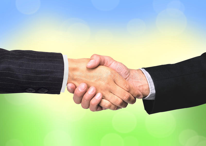 Handshakings over bright nature background. Conceptual photo of teamwork stock photos