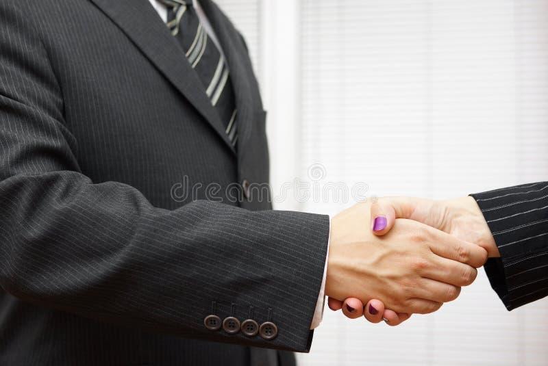 Handskakning av affärspartners, mannen och kvinnan i kontoret arkivbilder