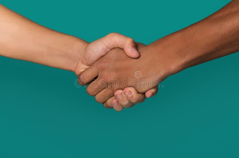 Handskakning av afro--amerikanen och caucasian tonåringhänder arkivbild