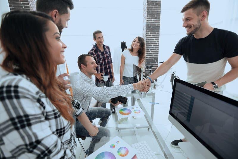 Handskakning av kollegor i ett idérikt kontor fotografering för bildbyråer