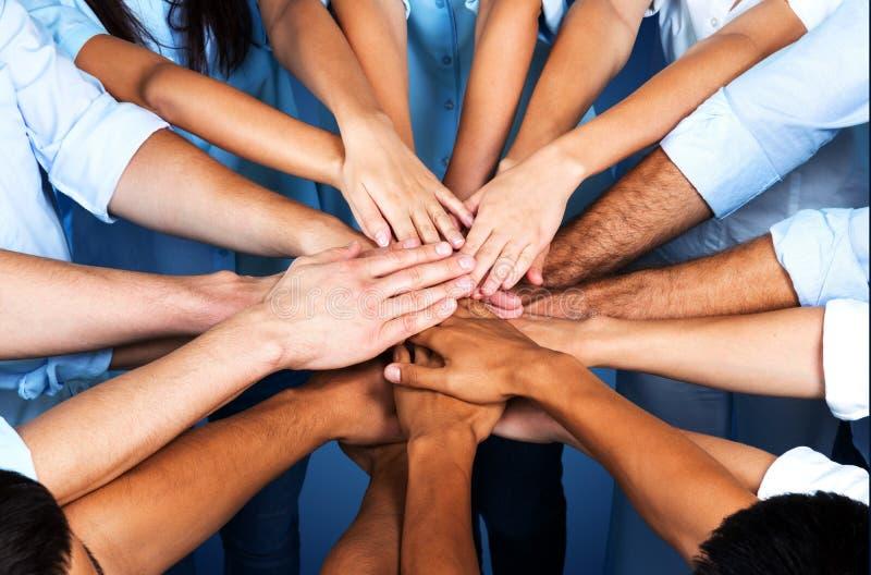 Handskakning av många unga affärspersoner, teamwork arkivbild