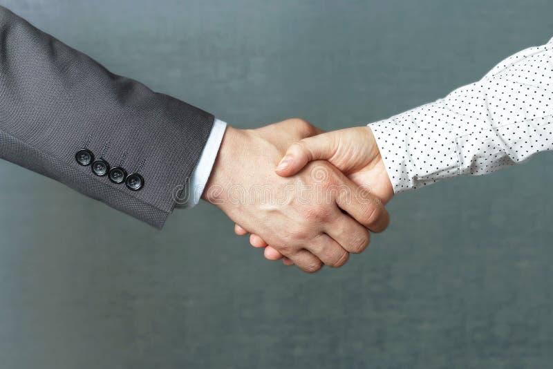 Handskakning av mannen och kvinnan i affärskläder, främre sikt för närbild arkivfoton