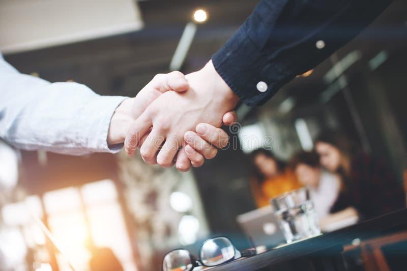 Handskakning av närbilden för två affärsmän, på en bakgrund av det moderna vindkontoret royaltyfria bilder