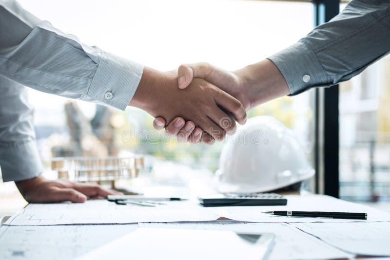 Handskakning av samarbete, konstruktionsteknik eller arkitekten att diskutera en ritning och en byggande modell, medan kontroller arkivfoton