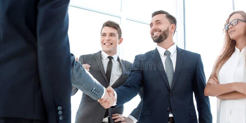 Handskakning av unga affärspartners i kontoret royaltyfri foto