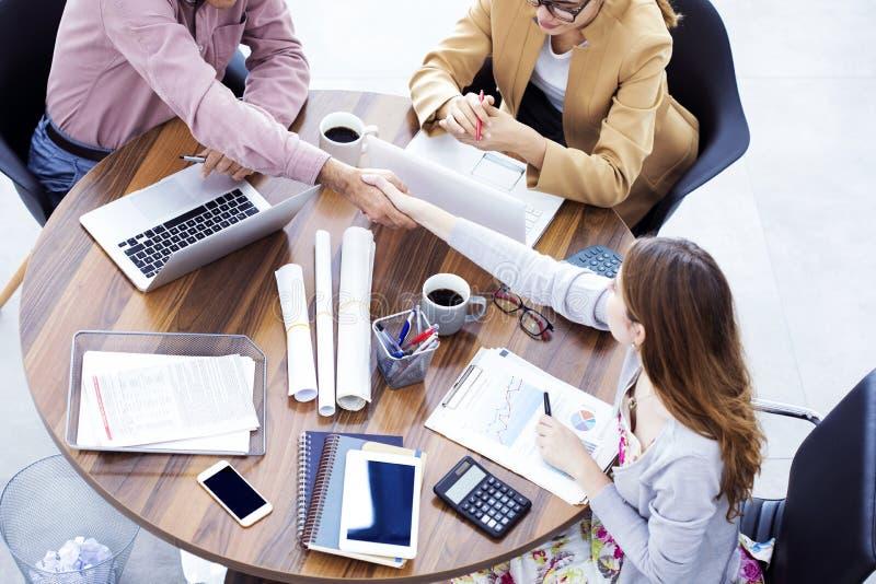 Handskakning för affärsfolk i kontoret royaltyfria bilder