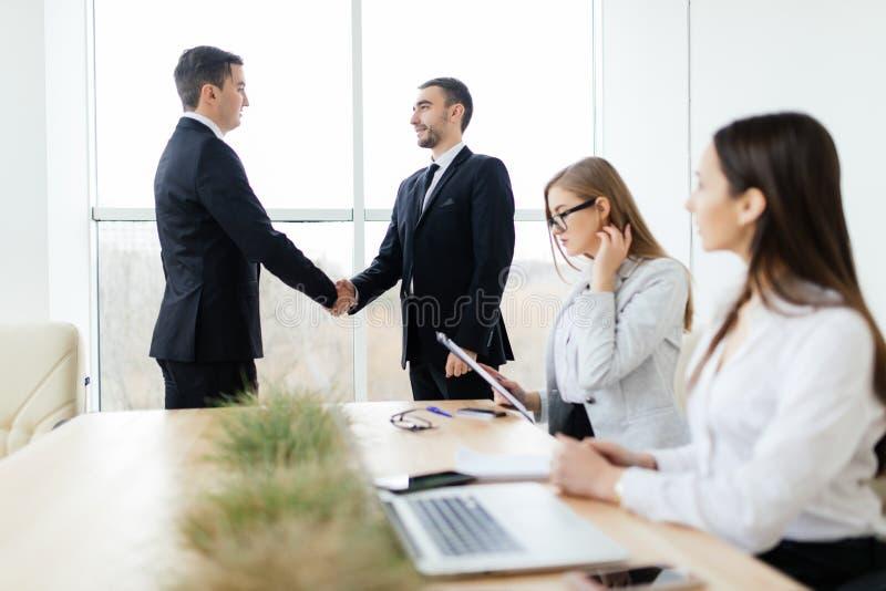 Handskakning för affärsfolk i mötesrum royaltyfria bilder
