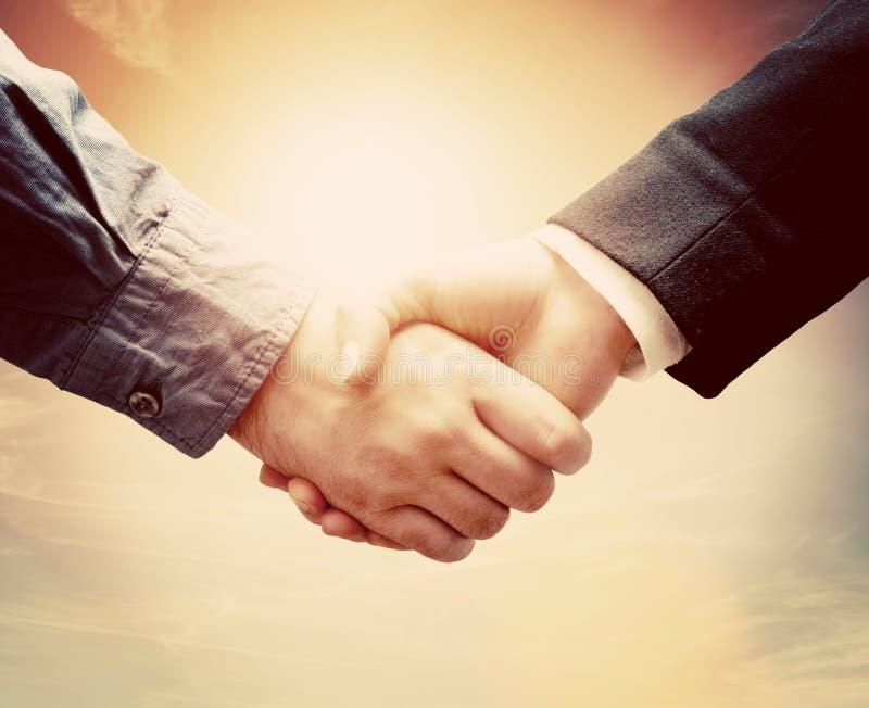 Handskakning för affärsfolk Solig tappninghimmel royaltyfri foto